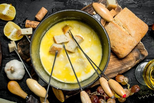 Deliziosa fonduta di formaggio con vino bianco sulla tavola rustica nera.