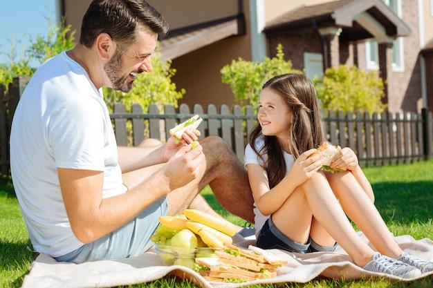 Cibo delizioso. felice piacevole padre e figlia seduti sul picnic e godersi i loro panini sorridendo a vicenda