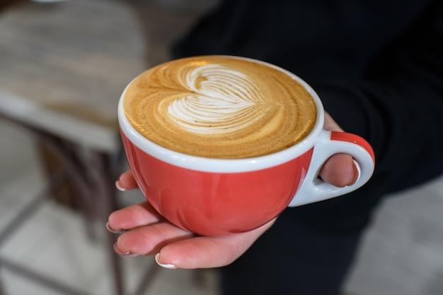 Delizioso e fragrante cappuccino nelle mani di una ragazza barista in un'accogliente caffetteria