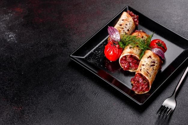 Tartaro di manzo fresco delizioso con toast su un piatto quadrato nero su uno sfondo scuro