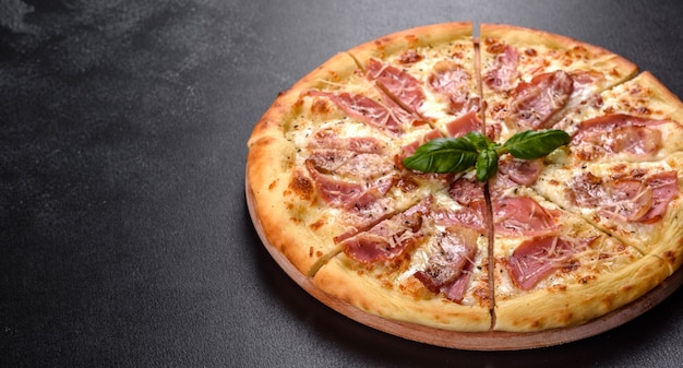 Deliziosa pizza fresca croccante dal forno con prosciutto, formaggio e basilico. cucina italiana