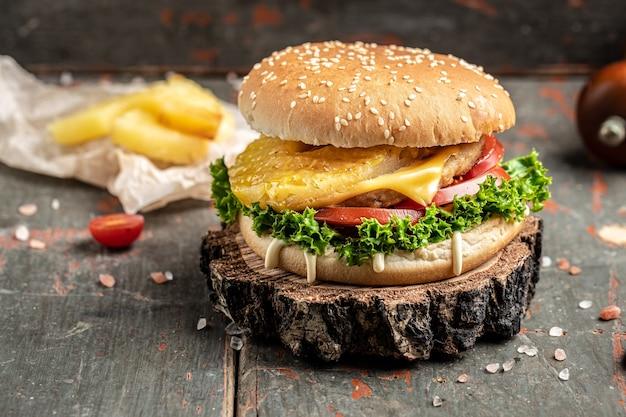 Hamburger casalingo fresco delizioso su una tavola di legno. cibo di strada. fast food e concetto di mangiare malsano. posto per il testo