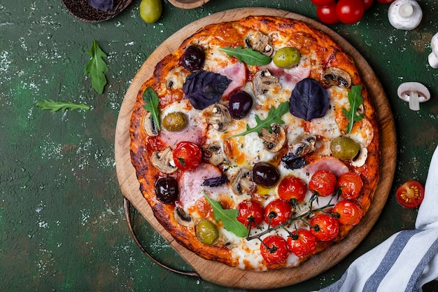 Deliziosa pizza fresca fatta in casa con prosciutto, funghi e pomodori