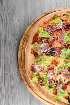 Deliziosa pizza italiana fresca con prosciutto, salame, pomodori, insalata e parmigiano su una tavola di legno su un tavolo di legno. vista dall'alto.