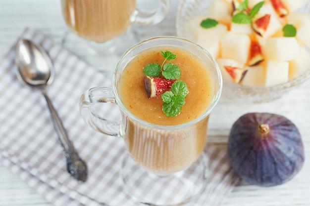 Un delizioso frullato di fichi e melone fresco in un bicchiere con una fetta di fico su fondo di legno bianco. concetto di cibo sano. Foto Premium