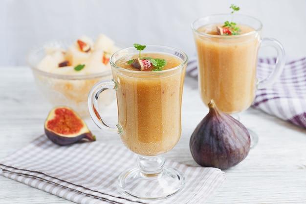 Un delizioso frullato di fichi e melone fresco in un bicchiere con una fetta di fico su fondo di legno bianco. concetto di cibo sano.