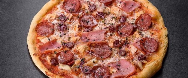 Deliziosa pizza da forno fresca con pomodori, salame e pancetta su uno sfondo scuro di cemento. cucina italiana