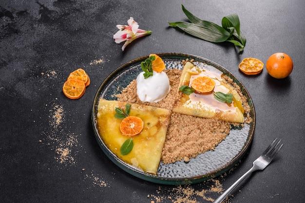 Deliziose frittelle fresche su un piatto con salsa dolce e gelato decorato con menta. deliziosa colazione abbondante