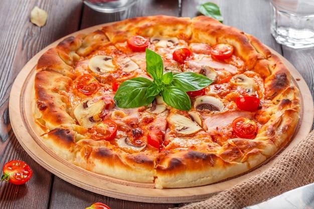 Pizza fresca deliziosa servita sulla tavola di legno Foto Premium
