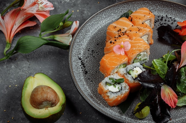 Rotoli di sushi freschi deliziosi con il salmone e il formaggio di philadelphia sul piatto grigio su fondo di pietra scuro. frutti di mare giapponesi tradizionali, concetto di cibo sano