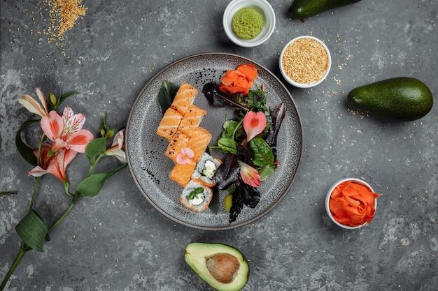 Deliziosi involtini di sushi freschi con salmone e formaggio philadelphia su lastra grigia