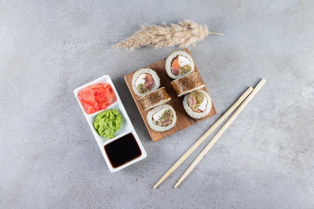 Deliziosi involtini di sushi freschi con salsa di soia e bacchette di legno posizionati su una tavola di legno.