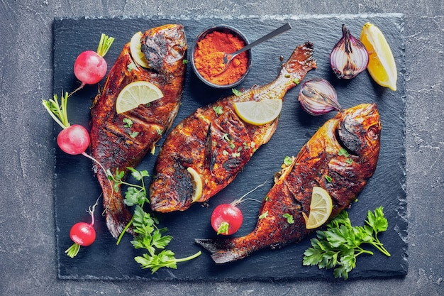 Delizioso pesce dorado appena grigliato servito su un vassoio di ardesia nera con ravanello, cipolla rossa grigliata e fette di limone su un tavolo di cemento, vista orizzontale dall'alto, spazio copia, flatlay, primo piano