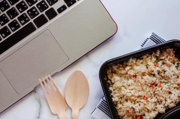Delizioso riso fritto in scatola di pranzo sulla biancheria intima con cucchiaio di legno e forchetta e computer portatile sul posto di lavoro