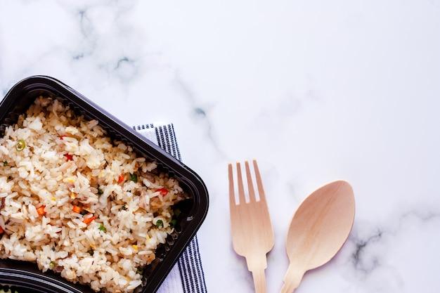Delizioso riso fritto in scatola di pranzo con cucchiaio, cucchiaio di legno e forchetta su fondo di marmo