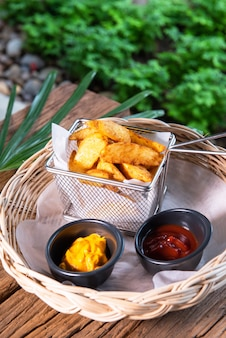 Deliziose patatine, servite con salsa ketchup e senape. disposto in un bellissimo cestino in rattan, posto su un tavolo di legno.