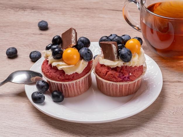 Deliziosi muffin alla frutta con frutti di bosco e cioccolato su un piatto bianco e una tazza rotonda di tè. colazione fatta in casa su un tavolo di legno.
