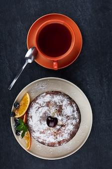 Deliziosa torta fruttata nel piatto con fette di arancia secca e una tazza di tè sulla superficie del tavolo scuro