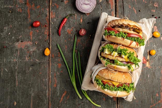 Deliziosi hamburger alla griglia su fondo di legno rustico. fast food e cibo spazzatura concetto, banner, menu, posto ricetta per testo, vista dall'alto,