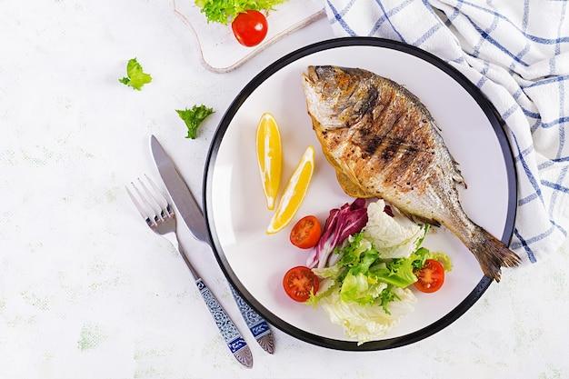 Delizioso dorado alla griglia o orata di mare con insalata, spezie, dorada alla griglia su un piatto