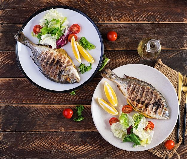 Delizioso dorado alla griglia o orata di mare con insalata, spezie, dorada alla griglia su un tavolo di legno
