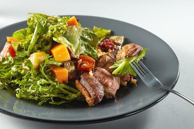 Deliziosa carne di anatra alla griglia con zucca arrosto con insalata su una forchetta