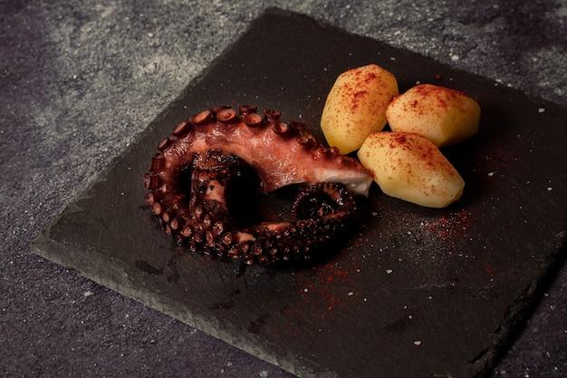 Deliziosi tentacoli di polpo alla griglia con patate condite con paprika spagnola, olio d'oliva e sale marino Foto Premium