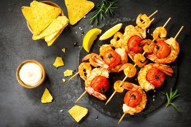 Deliziosi gamberi alla griglia con limone speziato e salsa serviti su una tavola di ardesia frutti di mare
