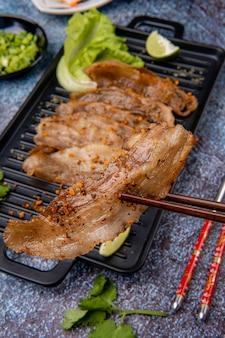 Deliziosa pancetta di maiale affettata alla griglia con piastratura di salsa barbecue o barbecue sul piatto