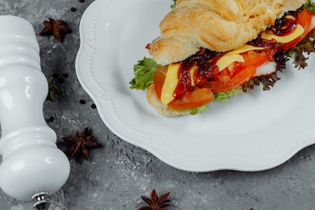 Delizioso croissant al prosciutto e formaggio cheddar con insalata.