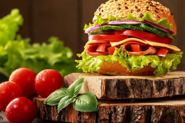 Delizioso panino prosciutto, formaggio e salame con verdure, lattuga, pomodorini in ambiente naturale con superficie in legno