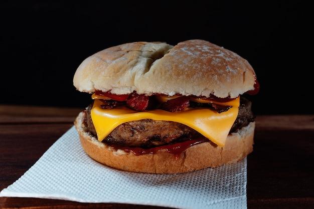Delizioso hamburger con pancetta e formaggio cheddar su pane fatto in casa con semi e ketchup su una superficie di legno e sfondo nero.