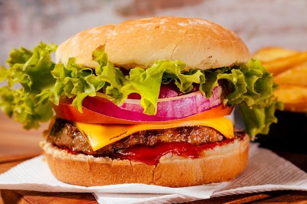 Delizioso hamburger con formaggio cheddar, lattuga, pomodoro, anelli di cipolla rossa e pancetta grigliata su pane fatto in casa accompagnato da spettacolari patate rustiche e salsa barbecue fatta in casa.