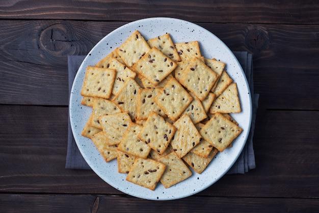 Deliziosi biscotti sani cracker con semi di lino e semi di sesamo su un piatto. sfondo di uno spuntino sano, tavolo in legno rustico scuro. copia spazio.