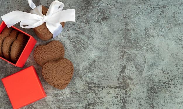 Deliziosi biscotti a forma di cuore in una scatola su un tavolo scuro, vista dall'alto con spazio per il testo. san valentino