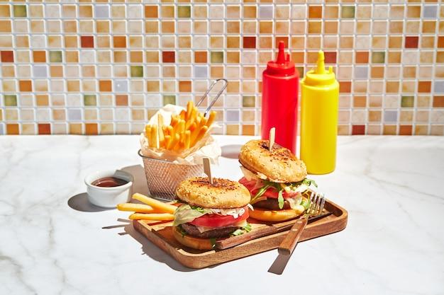 Deliziosi hamburger fatti in casa su vassoio di legno in condizioni di luce solare intensa hamburger