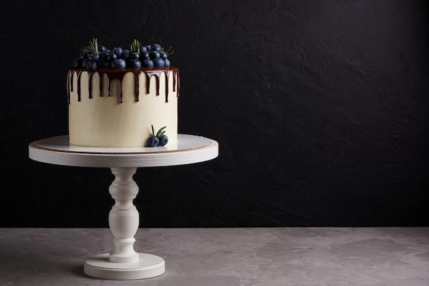Deliziosa torta fatta in casa decorata con mirtilli freschi su un supporto in legno bianco