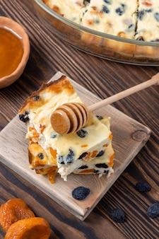 Deliziosa casseruola di formaggio fatta in casa con albicocche secche e uvetta versata con miele