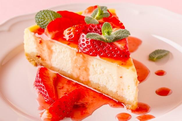 Deliziosa torta di formaggio fatta in casa con fragole su sfondo rosa.