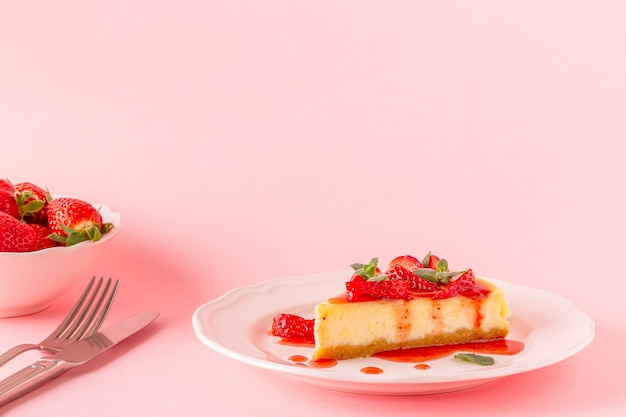 Deliziosa torta di formaggio fatta in casa con fragole sul rosa.