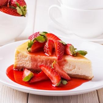 Deliziosa torta di formaggio fatta in casa con le fragole sulla tavola di legno bianca.