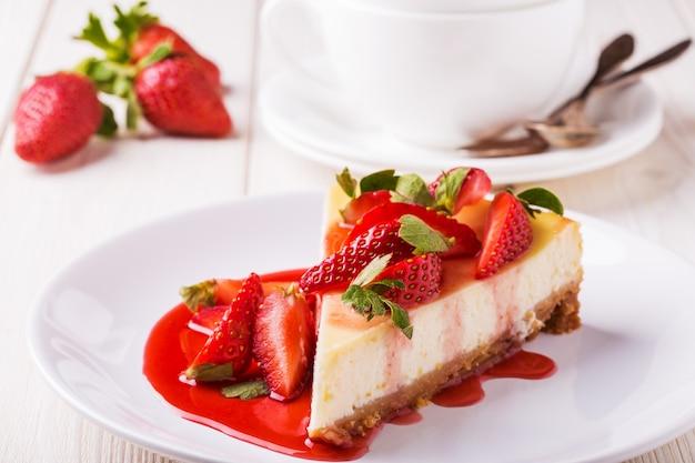 Cheesecake casalinga deliziosa con le fragole sulla tavola di legno bianca.