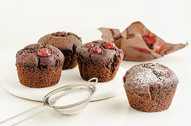 Bigné o muffin casalinghi deliziosi della ciliegia con zucchero in polvere sulla tavola bianca.