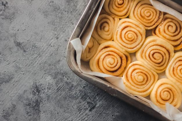 Pasta fatta in casa deliziosa del panino dei rotoli di cannella nella teglia a forma di rettangolo sullo sfondo di cemento grigio scuro.