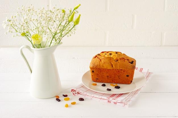 Torta di pagnotta fatta in casa deliziosa di ricotta e uvetta su fondo di legno rustico bianco.
