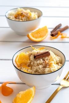 Delizioso cuscus fatto in casa con arance e cannella su fondo di legno rustico. gustoso cibo vegano.