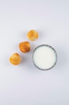 Deliziosi biscotti croccanti fatti in casa con una ciotola di latte su un tavolo bianco.