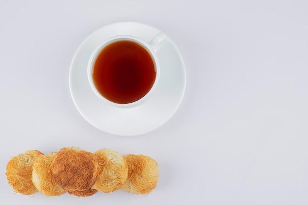 Deliziosi biscotti croccanti fatti in casa con una tazza bianca di tè caldo.