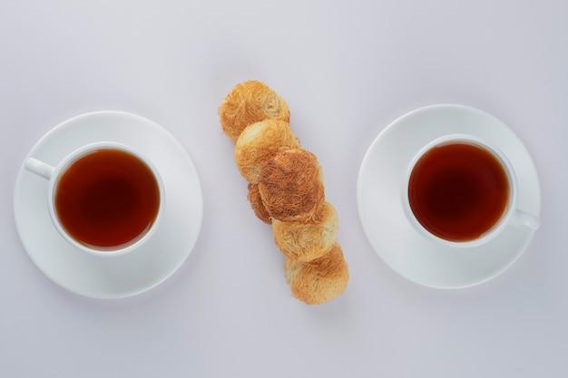 Deliziosi biscotti croccanti fatti in casa con tazze bianche di tè caldo.