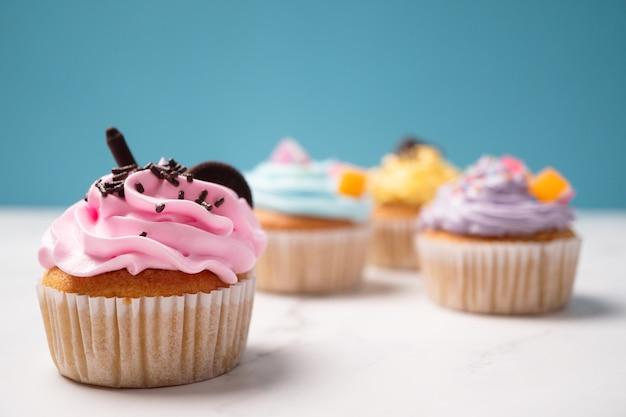 Deliziosi cupcakes fatti in casa con crema colorata e guarnire con caramelle e biscotti al cioccolato.